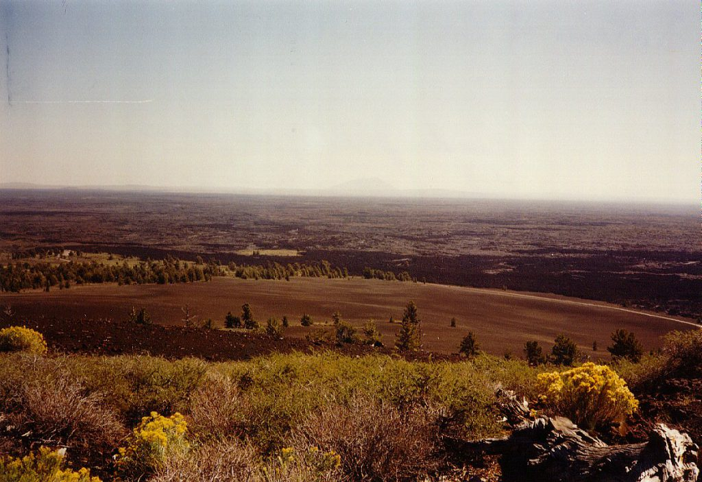 The extent of the lava flow and cinder cone activity can be seen in this view from the top of a large cinder cone. In the distant haze you can see another large cinder cone.