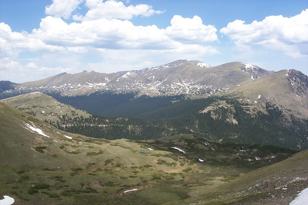 This photo shows an alpine valley nestled between the crest ridges of the Rocky Mountains. There are pockets of snow and we are at about 13,000 feet elevation.