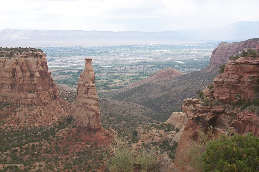 This photo shows the 'independence' fin. The fin is the remnant of a thin rock wall that originally extended from the far left to the far right. If you look closely you can see rain falling in the top right of the picture -- right over Grand Junction!