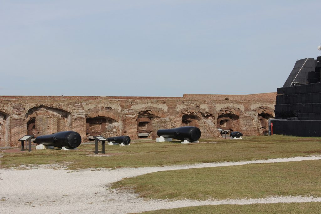A display of the various cannon sized used in the fort with the cannon rooms in the background. The large black walls to the right are in back of a large sand bank designed to absorb a pounding from large (distant) naval guns.