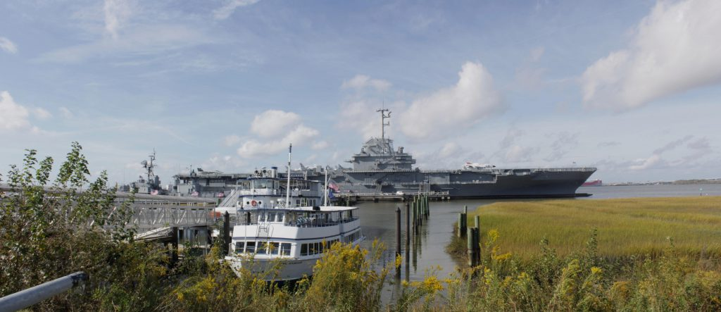 The ferry to Fort Sumter in the foreground at the loading deck with the Yorktown in the background.