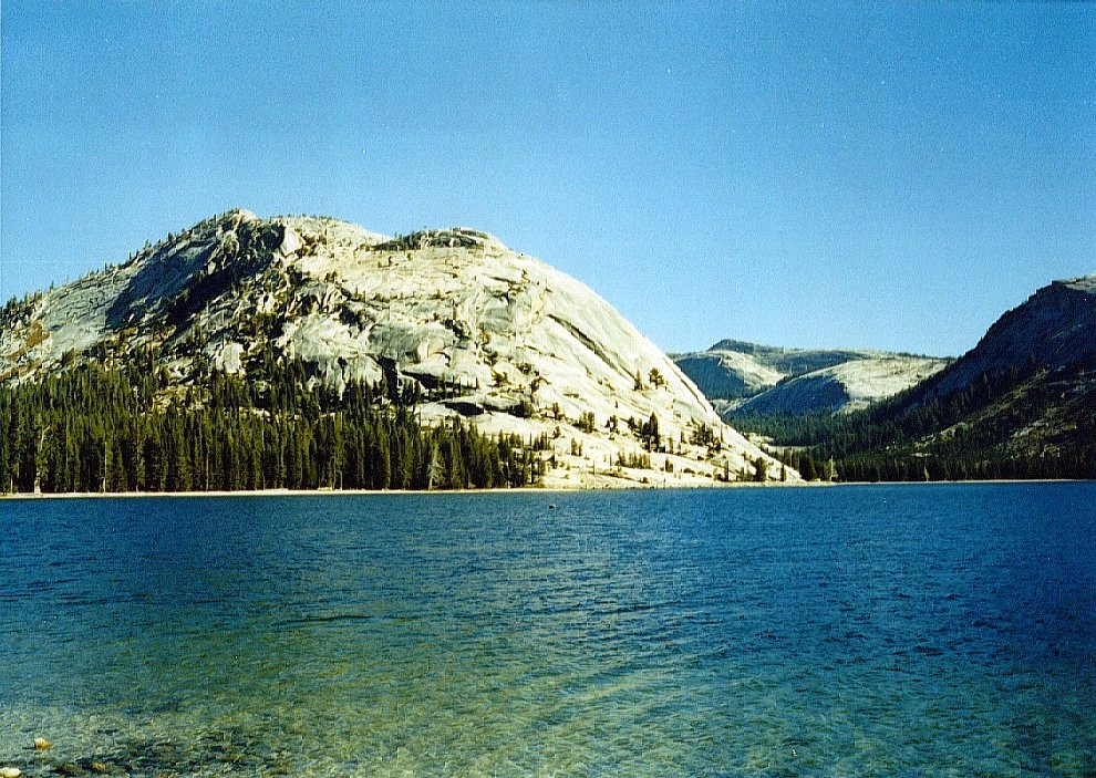 Tioga Lake. High up, just below the top of the pass, you will find a number of small lakes. The crystal clear blue colour of Tioga Lake shows very well in the photo below. The view is eastward to the crest of the Sierra Nevada range.