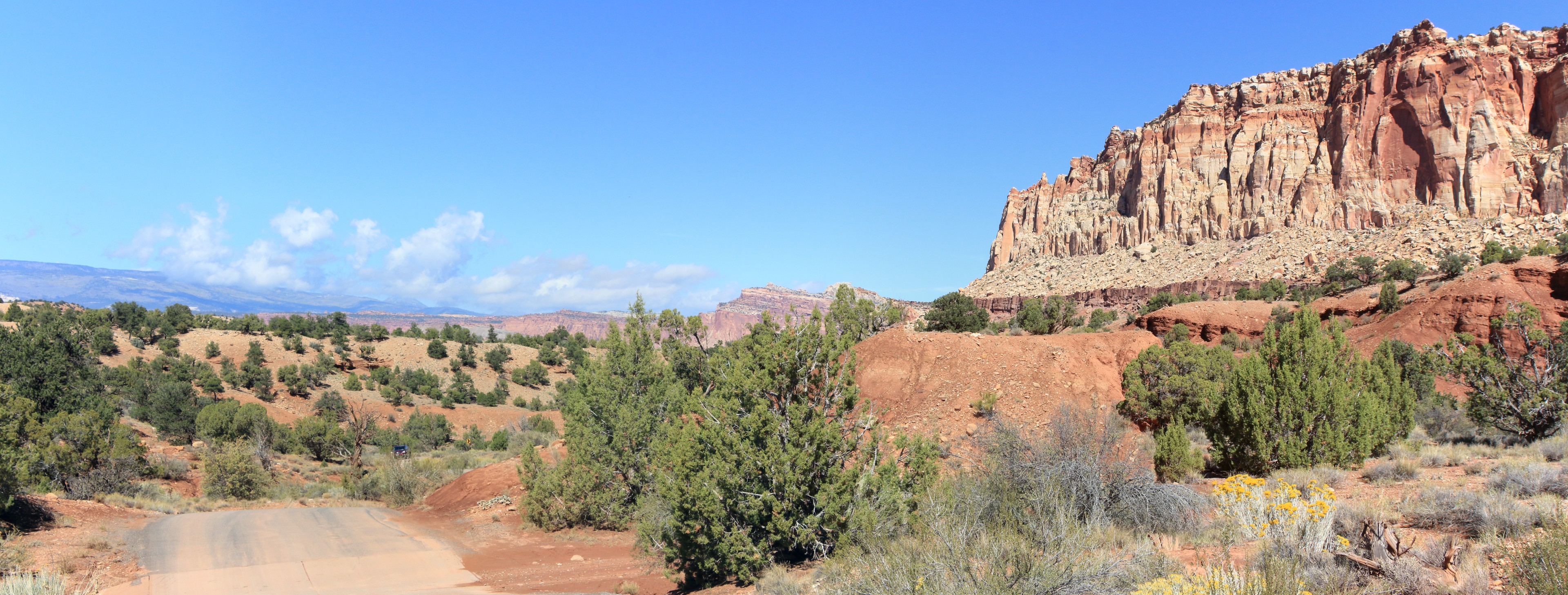 Another Long View North. This long view is taken from near the entrance to the Capitol Gorge. Although the reed extent is not a visible as it is in some of the other views, a large context is available from the high walls of the reef on the right, through the extent of the reef running north, the rise of Boulder mountain in the distant left and the colourful desert valley in between.