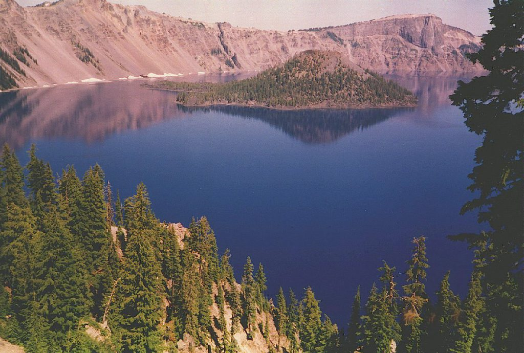 This photograph, also taken from the west rim looks out over the lake and shows Wizard Island. Wizard Island is actually the 'crater' of Crater Lake. You can see the crater in the top of the cinder cone which is the island. This photo is taken at sunset hence the pink coloration.