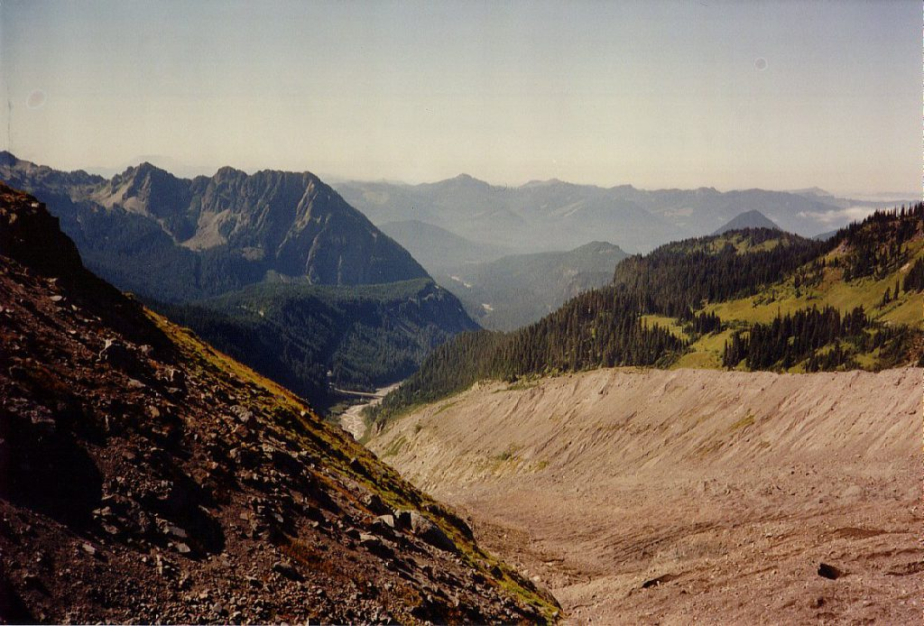 Here is the view from up near the glacier -- it is to the lower right out of site beneath piles of dirt and rock in this photo. You can see the moraine walls left and right and the river bed far below. The road to Paradise crosses the river on the bridge visible far below.